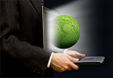 Green business. Businessman with an open laptop and a green earth globe coming out of the screen Stock Photography