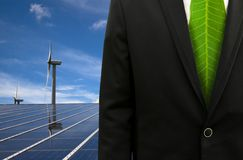 Green Business and eco energy. Bussinessman with leaf tie and solar panel and windmill Stock Photos