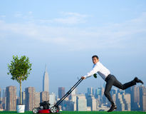 Green Businessman in the City mowing lawn Stock Photos