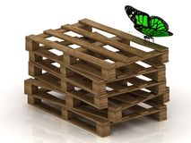 Green butterfly is sitting on a stack of wooden pallets Royalty Free Stock Image