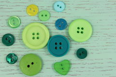 Green buttons haberdashery on a green wooden background Royalty Free Stock Images
