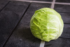Green cabbage isolated on black wood background. royalty free stock photos