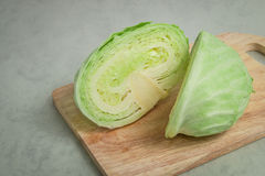 Green cabbage on wood cutting board Royalty Free Stock Images
