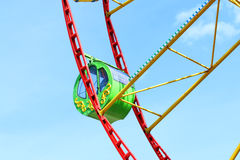Green cabin of colorful Ferris wheel and blue sky Royalty Free Stock Images