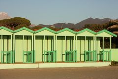 Green cabins in a neat, geometric row. Italian bathhouse in Tuscany on the beach by the sea.  stock images