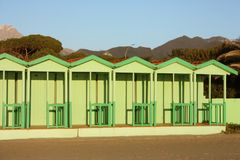 Green cabins in a neat, geometric row. Italian bathhouse in Tuscany on the beach by the sea.  stock photography