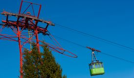 Green cable car speeding upwards. Some fir trees seen lower left.  stock images