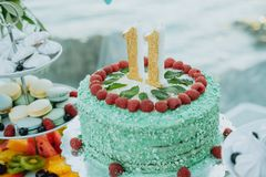 Green cake with number 11 on the table stock photos