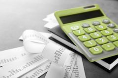 Green calculator with bills and notebook. On gray background. Tax concept royalty free stock image