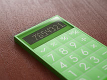 Green calculator on wooden table Stock Photos