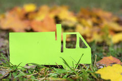 Green camion on an autumn background.Eco friendly. Paper cut of camion on a green grass .Eco concept royalty free stock photography