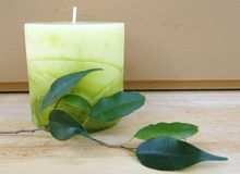 Green candle. Big green candle and leafs on a wooden table Stock Photography