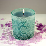 Green Candle and Sea Salt - Top View. Green candle with purple aromatic sea salt Stock Photo