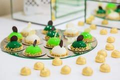 Green candy bar with balls, macaroon at the wedding stock photos