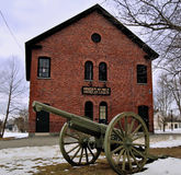 Green cannon in front of an old brick building on a green in town. WWI, WWII, bleak mid winter day, blue gray sky, grass and partially snow covered field royalty free stock photography