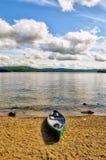 Green canoe on lake shore Royalty Free Stock Photo