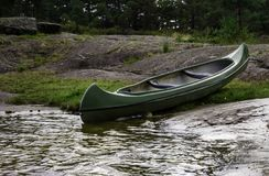Green Canoe. On land by a lake in the forest Stock Photos