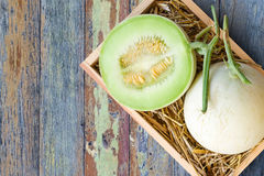 Green cantaloupe melon in wood box. On wood background royalty free stock photos
