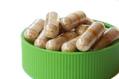 Green cap full of vitamin pills Royalty Free Stock Image