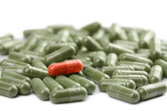Green capsule pills with red one isolated Royalty Free Stock Photos