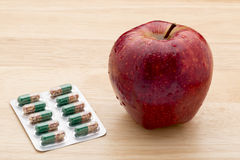 Green capsules bliter pack and fresh red apple Stock Photo