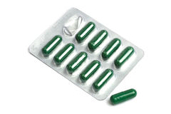 Green capsules packed in blister royalty free stock photography