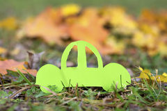 Green car on an autumn background.Eco friendly. Paper cut of car on green grass .Eco concept stock image