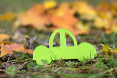 Green car on an autumn background.Eco friendly. Paper cut of car on green grass .Eco concept royalty free stock photography