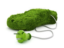 Green car covered with grass texture connected to the electric plug Stock Photos