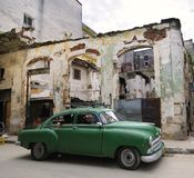 Green car on eroded havana street, cuba. Green classic american car in havana street with eroded buildings in the background stock image