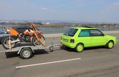 Green Car with Orange Dirt Bike on Theodor Heuss Bridge Stock Photo