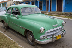 Green car parked on street in Vinales, Cuba. Old Classic Green Car parked on the main street in the village of Vinales, Cuba Royalty Free Stock Image