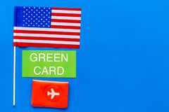 Green card text near passport cover and USA flag top view on blue background copy space. Immigration to United states of. America stock photo
