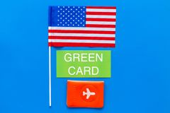 Green card text near passport cover and USA flag top view on blue background copy space. Immigration to United states of. America royalty free stock images