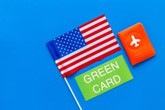 Green card text near passport cover and USA flag top view on blue background copy space. Immigration to United states of. America stock photos
