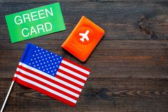 Green card text near passport cover and USA flag top view on dark wooden background copy space. Immigration to United. States of america stock images