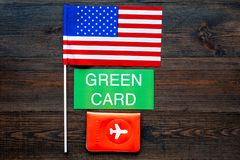 Green card text near passport cover and USA flag top view on dark wooden background copy space. Immigration to United. States of america royalty free stock photography