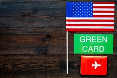 Green card text near passport cover and USA flag top view on dark wooden background copy space. Immigration to United. States of america royalty free stock images
