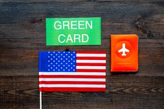 Green card text near passport cover and USA flag top view on dark wooden background. Immigration to United states of. America stock photo