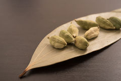 Green cardamom in dried Indian bay leaves on a black background Stock Photos