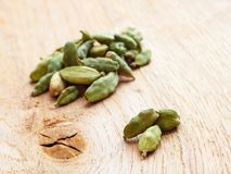 Green cardamom pods on wooden background Stock Image