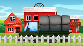 A green cargo in front of a barn inside the fence Royalty Free Stock Photo