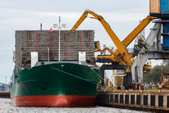 Green cargo ship. Loading in the port of Riga, Europe Stock Photo
