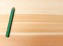 Green carpentry pencil on wood. Green carpenter pencil on a wood background with copy space Stock Photos