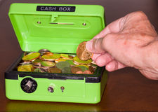Green cash box with gold and silver coins. Green cash box with combination lock open to show piles of coins including gold and silver stock image