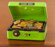 Green cash box with gold and silver coins. Green cash box with combination lock open to show piles of coins including gold and silver stock photography