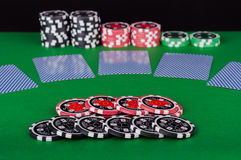 Green casino table with covered playing cards, red and black chi Stock Images