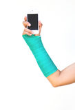 Green cast on hand and arm, holding mobile phone. Stock Photos