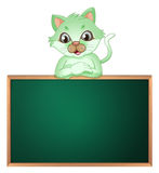 A green cat leaning above the blackboard Stock Images