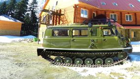 Green caterpillar all-terrain vehicle against the backdrop of chalets and firs in the mountains stock footage